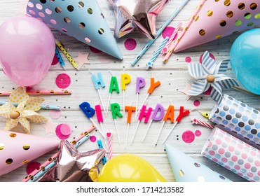 Text Happy Birthday by candle  letters with birthday asseccories, candles and confetti  on white wooden  background. Top view, flat lay.