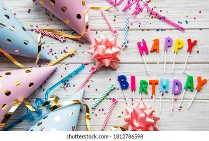 Text Happy Birthday by candle  letters with birthday asseccories, candles and confetti  on white wooden background