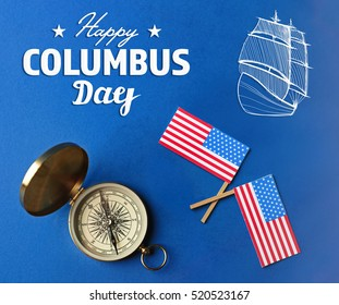 Text HAPPY COLUMBUS DAY with compass and USA flags on blue background. National holiday concept.