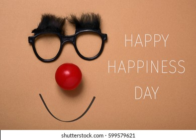 the text happy happiness day, and a pair of eyeglasses with bushy eyebrows, a red clown nose and a smile drawn on a brown background