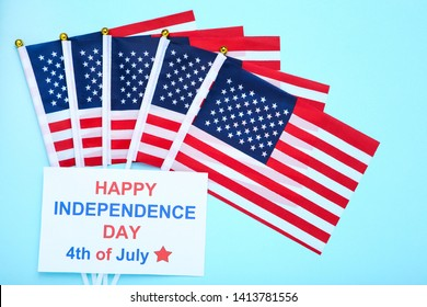 Text Happy Independence Day 4th of July with american flages on blue background