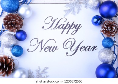 Text Happy New Year on paper with fur-tree, branches, colored glass balls , decoration and cones on a wooden background