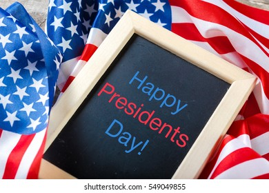 the text happy presidents day written in a chalkboard and a flag of the United States