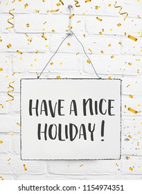 Text have a nice holiday white sign banner board with golden confetti on white brick background