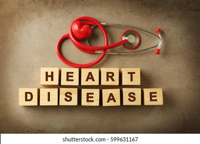 Text HEART DISEASE made of wooden cubes and stethoscope on color background