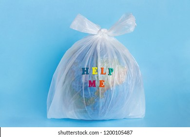 Text Help me and Model planet Earth in polyethylene plastic disposable package on blue background. Ecology problems Concept pollution of environment with polyethylene plastic waste World Earth Day