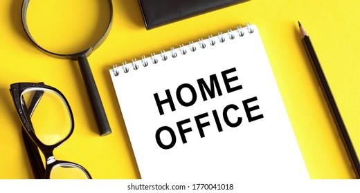 Text HOME OFFICE in Notebook. Stift und Brille und Lupe auf gelbem Tisch. Konzept