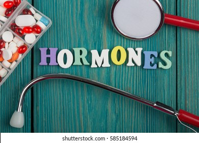 "Text ""Hormones"" of colored wooden letters, stethoscope and pills on a blue wooden background"