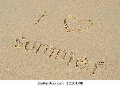 The text 'I love summer' written in the sand at a tropical beach
