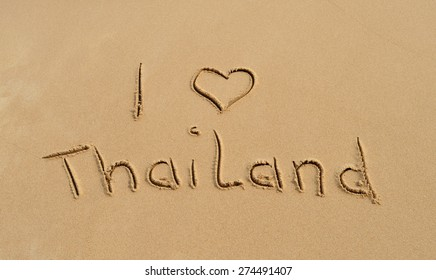 The text 'I love Thailand' written in the sand at a tropical beach
