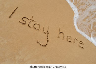 The text 'I stay here' written in the sand at a tropical beach