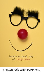 the text international day of happiness, and a pair of eyeglasses with bushy eyebrows, a red clown nose and a smile drawn on a yellow background
