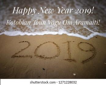 Text label with blurred background of sandy beach, kadazan language for happy new yepar 2019