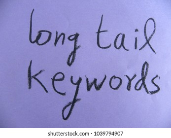 Text long tail keywords hand written by black oil pastel on purple color paper