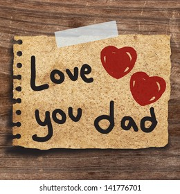 Text love you Dad for father's day  with  red heart on short note vintage paper with tape on the old wood wall background