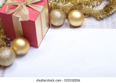 Text merry christmas on paper with balls and gift box.