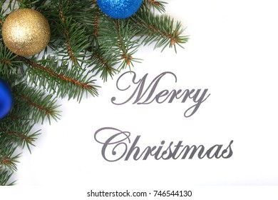 Text merry christmas on paper with fur-tree, branches, colored glass balls , decoration and cones on a wooden background