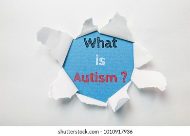 Text message What is autism on torn paper background.