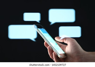 Text messages in cellphone screen with abstract hologram speech bubbles. Instant messaging app. Texting, group chat, sexting or sms concept. Customer service help desk with live support chatbot. - Shutterstock ID 1452139727