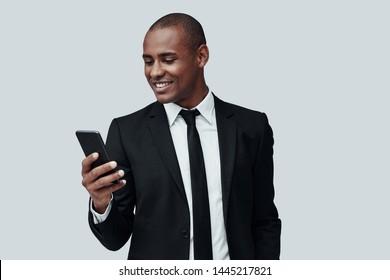 Text messaging. Charming young African man in formalwear using smart phone and smiling while standing against grey background