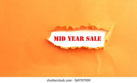 Text MID YEAR SALE appearing behind torn paper
