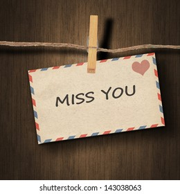 text miss you on the old envelope and clothes peg wood background