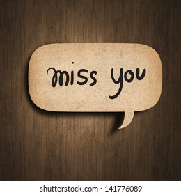 Text miss you on the speedch bubble paper on wood background