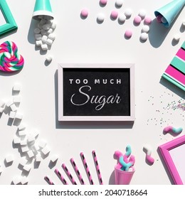Text Too Much Sugar. Excess of sweets, chocolate, candy, sweet food. Various tasty snacks in pastel colors, pink, mint green, on white background. Text on blackboard, chalk board. Sugar tax concept.