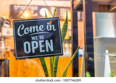 """Text on vintage black sign """"Come in we're open"""" in cafe."""