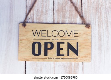 """Text on vintage wooden sign """"Come in we're open. grunge image hanging on a white door."""