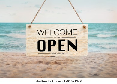 """Text on wooden sign """"Come in we're open"""" on the beach"""