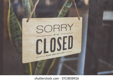 """Text on wooden sign """"Sorry we're closed """" in cafe and restaurant."""