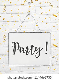Text party board with golden confetti metal plate white brick background