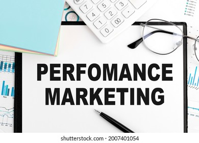 Text Perfomance Marketing on clipboard, pen, glasses, calculator, sticker, graphs. Business concept. Flat lay.