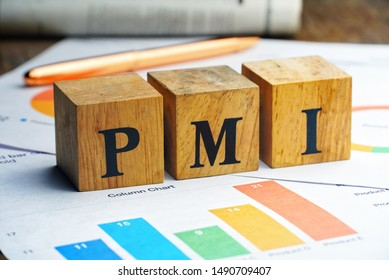 """Text """"PMI"""" on wood cube lay on chart candle document paper , economic data concept."""