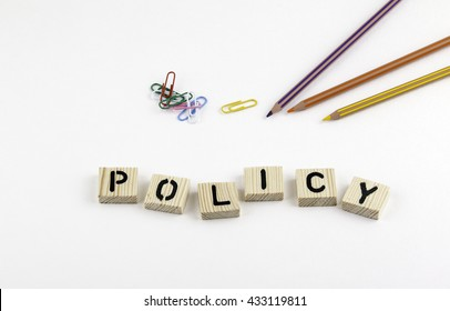 Text: Policy from wooden letterson on white office desk