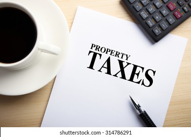 Text Property Taxes is on the white paper with coffee, calculator and ball pen aside.