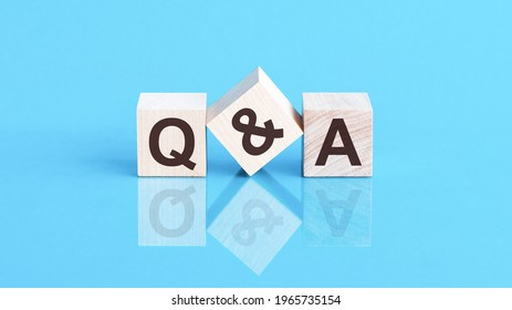 the text q and a written on the cubes in black letters, the cubes are located on a blue glass surface. Concept word forming with cube on background - questions and answers