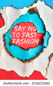 """Text """"Say no to fast fashion"""" in hole burned though white, red and turquoise paper"""
