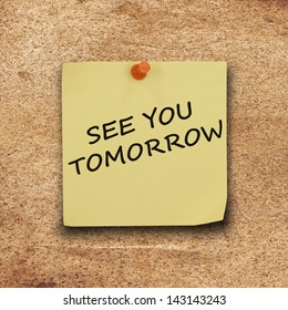 text see you tomorrow on  note paper and pin on the old hard paper board