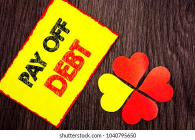 Text showing Pay Off Debt. Business photo showcasing Reminder To Paying Owed Financial Credit Loan Bills written Sticky Note Paper with Love Heart Next to it the wooden background.