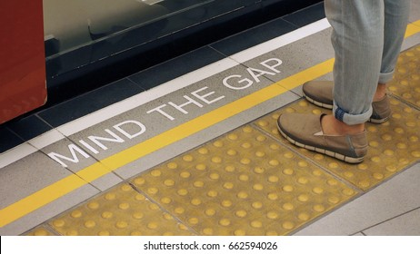 """Text sign on floor between train and platform """"Mind the gap"""" with white color and high angle view."""