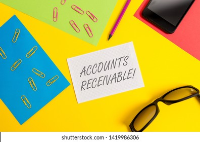 Text sign showing Accounts Receivable. Conceptual photo Legal Claim of Payment Money Owed to by Debtors Paper sheets pencil clips smartphone eyeglasses notebook color background.