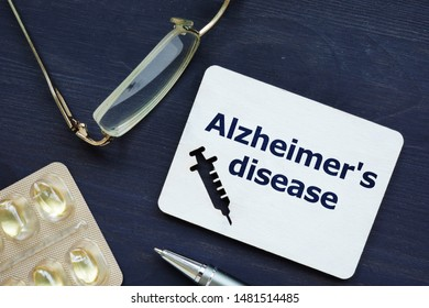 Text sign showing Alzheimer's disease. The text is written on a small wooden board with syringe silhouette. There are pills, blister, glasses, table on the photo.