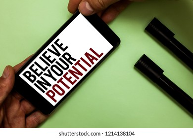Text sign showing Believe In Your Potential. Conceptual photo Have self-confidence motiavate inspire yourself Man's hand hold iPhone with black and red words near two black marker.