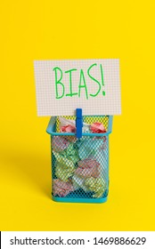 Text sign showing Bias. Conceptual photo inclination or prejudice for or against one demonstrating group Trash bin crumpled paper clothespin empty reminder office supplies yellow.