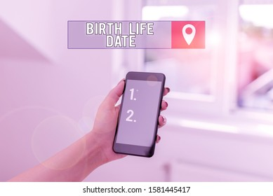 Text sign showing Birth Life Date. Conceptual photo Day a baby is going to be born Maternity Pregnancy Give life woman using smartphone office supplies technological devices inside home.