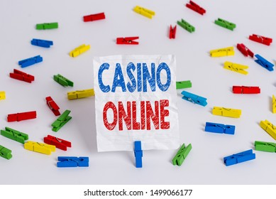 Text sign showing Casino Online. Conceptual photo Computer Poker Game Gamble Royal Bet Lotto High Stakes Colored clothespin papers empty reminder white floor background office.