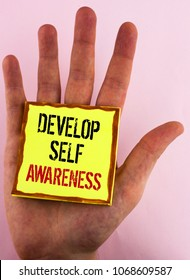 Text sign showing Develop Self Awareness. Conceptual photo What you think you become motivate and grow written Yellow Sticky Note Paper placed the Hand the plain background.