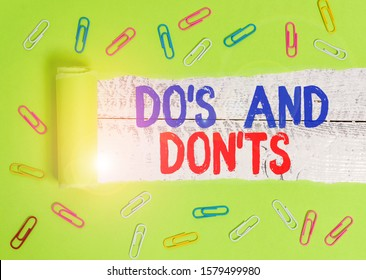 Text sign showing Do S And Don Ts. Conceptual photo Technologically complication of making a decision Paper clip and torn cardboard placed above a wooden classic table backdrop.
